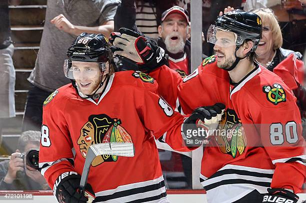 Patrick Kane and Antoine Vermette of the Chicago Blackhawks celebrate after Kane scored an empty net goal in the third period against the Minnesota...