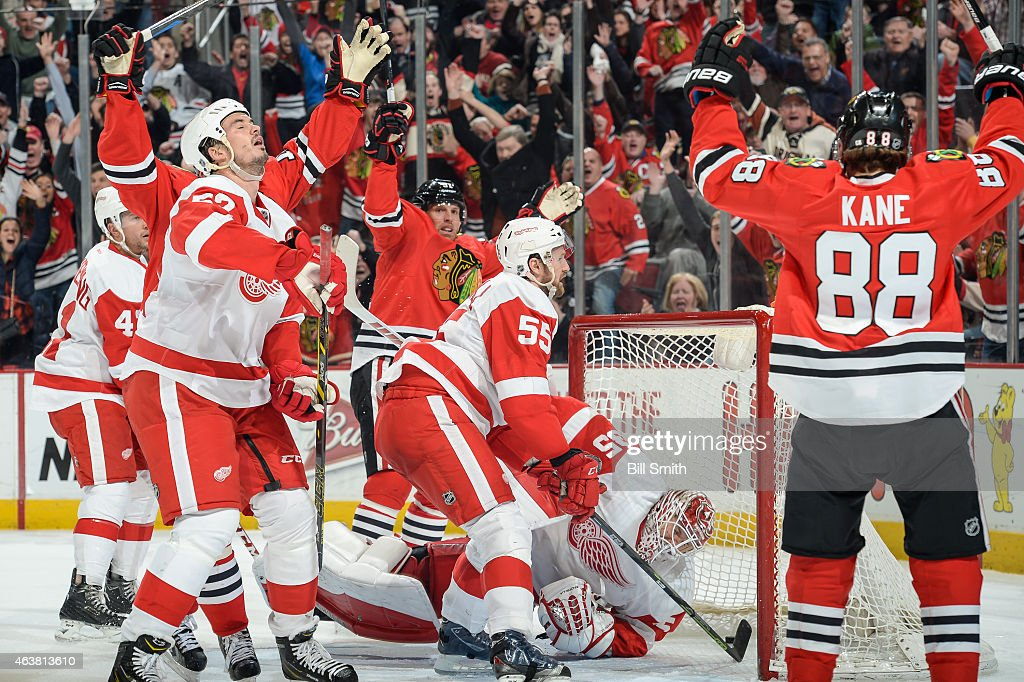 Patrick Kane #88 and Brad Richards #91 of the Chicago Blackhawks celebrate after scoring against the Detroit Red Wings in the third period, as Jonathan Ericsson #52 reacts behind Niklas Kronwall #55 during the NHL game at the United Center on February 18, 2015 in Chicago, Illinois.