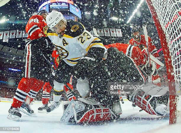 Patrick Kane and goaltender Corey Crawford of the Chicago Blackhawks defend the net against Chris Kelly of the Boston Bruins in Game Five of the 2013...