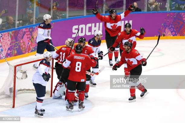 Patrick Kane and Zach Parise of the United States react as Carey Price Drew Doughty and Sidney Crosby of Canada celebrate after defeating the United...