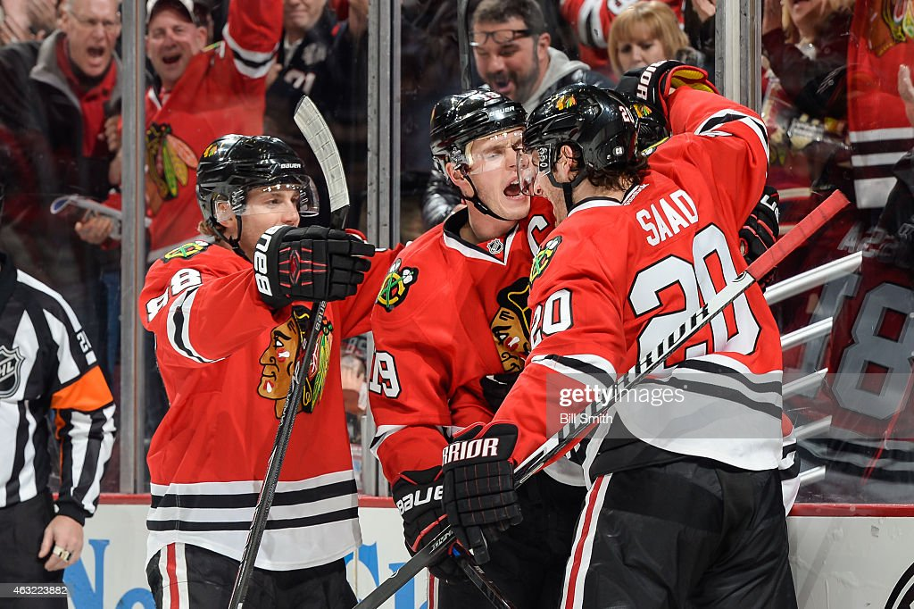<a gi-track='captionPersonalityLinkClicked' href=/galleries/search?phrase=Patrick+Kane&family=editorial&specificpeople=1977261 ng-click='$event.stopPropagation()'>Patrick Kane</a> #88, <a gi-track='captionPersonalityLinkClicked' href=/galleries/search?phrase=Jonathan+Toews&family=editorial&specificpeople=537799 ng-click='$event.stopPropagation()'>Jonathan Toews</a> #19 and <a gi-track='captionPersonalityLinkClicked' href=/galleries/search?phrase=Brandon+Saad&family=editorial&specificpeople=7128385 ng-click='$event.stopPropagation()'>Brandon Saad</a> #20 of the Chicago Blackhawks react after scoring against the Vancouver Canucks in the third period during the NHL game at the United Center on February 11, 2015 in Chicago, Illinois.