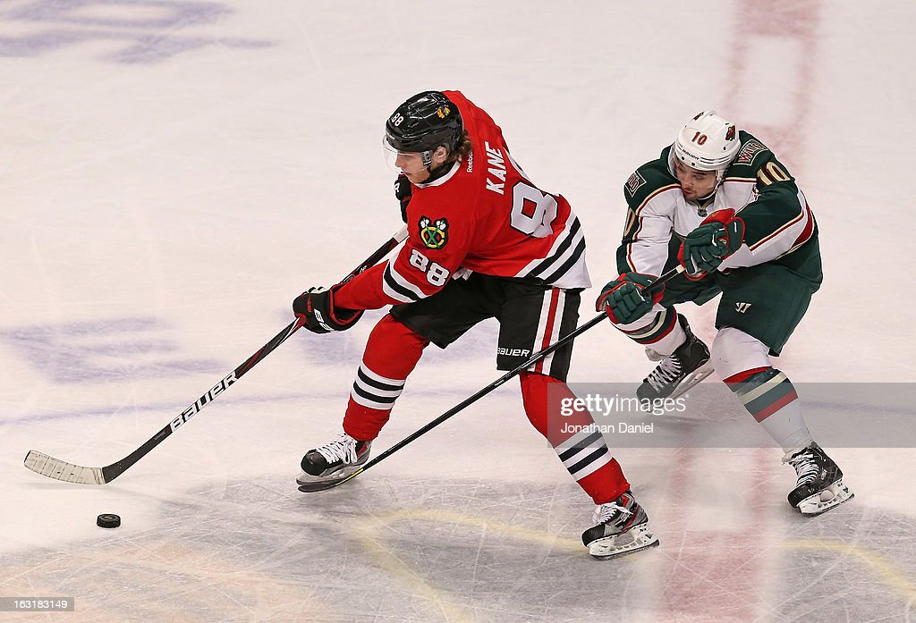Patrick Kane #88 of the Chicago Blackhawks advances the puck under pressure from <a gi-track='captionPersonalityLinkClicked' href=/galleries/search?phrase=Devin+Setoguchi&family=editorial&specificpeople=2221039 ng-click='$event.stopPropagation()'>Devin Setoguchi</a> #10 of the Minnesota Wild at the United Center on March 5, 2013 in Chicago, Illinois. The Blackhawks defeated the Wild 5-3.