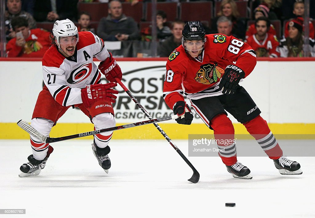 Patrick Kane #88 of the Chicago Blackhawks and Justin Faulk #27 of the Carolina Hurricanes chase the puck at the United Center on December 27, 2015 in Chicago, Illinois.