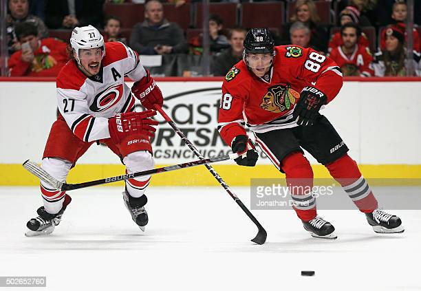 Patrick Kane of the Chicago Blackhawks and Justin Faulk of the Carolina Hurricanes chase the puck at the United Center on December 27 2015 in Chicago...