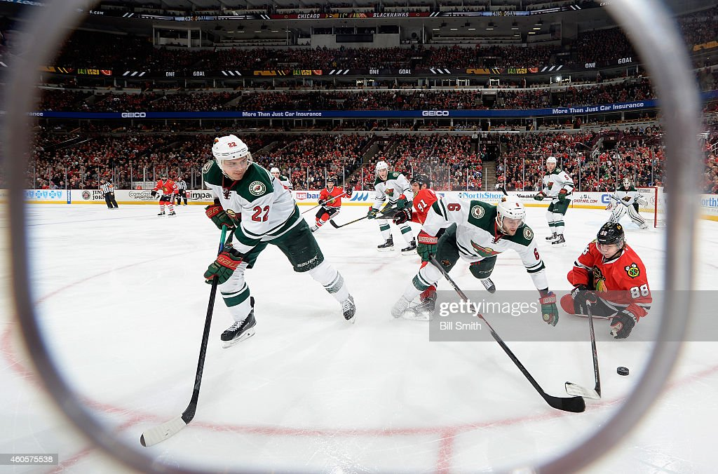 Patrick Kane #88 of the Chicago Blackhawks and Marco Scandella #6 of the Minnesota Wild scramble for the puck as Nino Niederreiter #22 watches from the left during the NHL game at the United Center on December 16, 2014 in Chicago, Illinois.