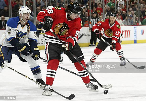 Patrick Kane of the Chicago Blackhawks approaches the puck as Barret Jackman of the St Louis Blues follows behind and Fernando Pisani of the...