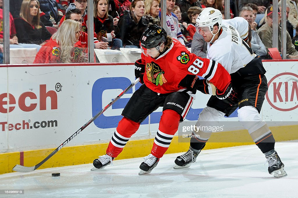 Patrick Kane #88 of the Chicago Blackhawks approaches the puck as <a gi-track='captionPersonalityLinkClicked' href=/galleries/search?phrase=Cam+Fowler&family=editorial&specificpeople=5484080 ng-click='$event.stopPropagation()'>Cam Fowler</a> #4 of the Anaheim Ducks pushes from behind during the NHL game on March 29, 2013 at the United Center in Chicago, Illinois.
