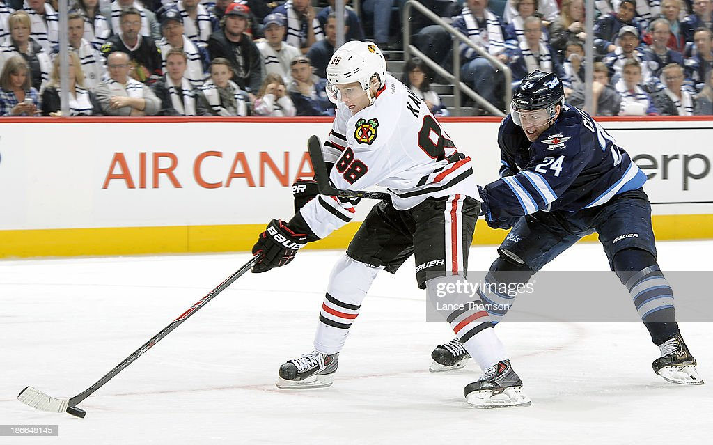 Patrick Kane #88 of the Chicago Blackhawks breaks into the offensive zone with the puck as <a gi-track='captionPersonalityLinkClicked' href=/galleries/search?phrase=Grant+Clitsome&family=editorial&specificpeople=4596638 ng-click='$event.stopPropagation()'>Grant Clitsome</a> #24 of the Winnipeg Jets gives chase during third period action at the MTS Centre on November 2, 2013 in Winnipeg, Manitoba, Canada.