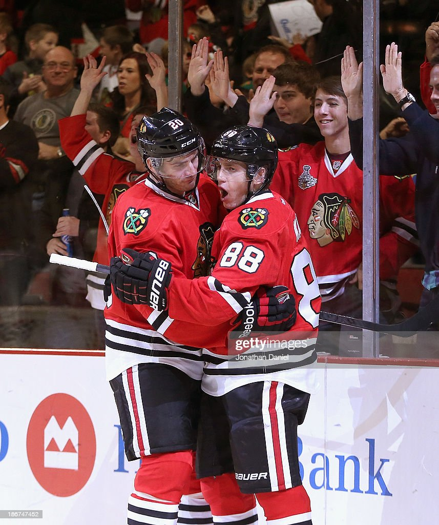 Patrick Kane #88 of the Chicago Blackhawks celebrates his second period goal with Brandon Saad #20 against the Calgary Flames at the United Center on November 3, 2013 in Chicago, Illinois.