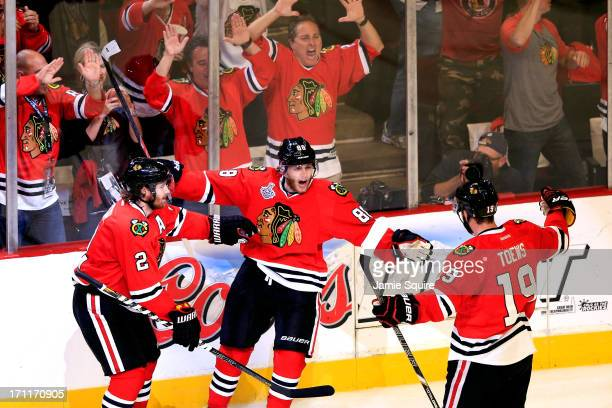 Patrick Kane of the Chicago Blackhawks celebrates with Jonathan Toews and Duncan Keith after he scored a goal in the second period against Tuukka...