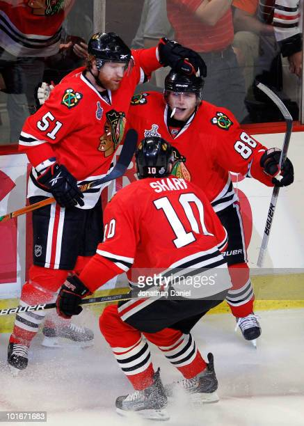 Patrick Kane of the Chicago Blackhawks celebrates with teammates Brian Campbell and Patrick Sharp after scoring a goal in the second period against...