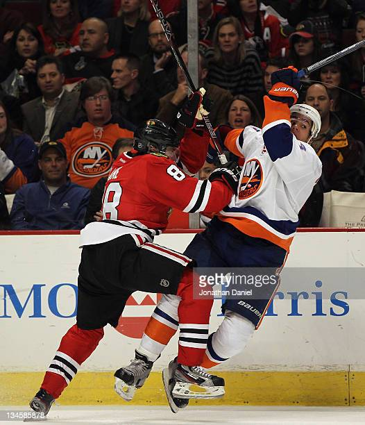 Patrick Kane of the Chicago Blackhawks checks Travis Hamonic of the New York Islanders at the United Center on December 2 2011 in Chicago Illinois...