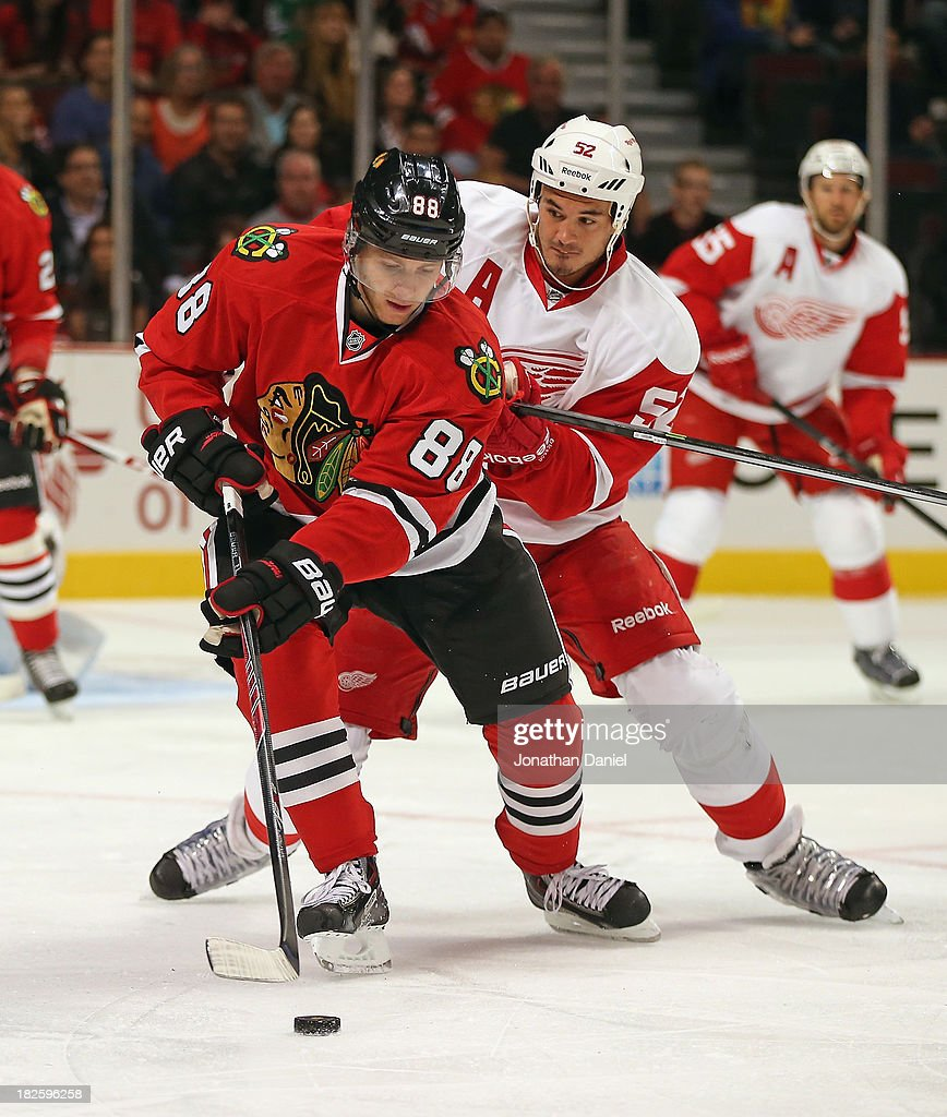 Patrick Kane #88 of the Chicago Blackhawks controls the puck under pressure from <a gi-track='captionPersonalityLinkClicked' href=/galleries/search?phrase=Jonathan+Ericsson&family=editorial&specificpeople=2538498 ng-click='$event.stopPropagation()'>Jonathan Ericsson</a> #52 of the Detroit Red Wings during an exhibition game at United Center on September 17, 2013 in Chicago, Illinois. The Blackhakws defeated the Red Wings 2-0.