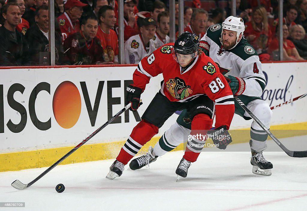 Patrick Kane #88 of the Chicago Blackhawks controls the puck under pressure from <a gi-track='captionPersonalityLinkClicked' href=/galleries/search?phrase=Clayton+Stoner&family=editorial&specificpeople=2222214 ng-click='$event.stopPropagation()'>Clayton Stoner</a> #4 of the Minnesota Wild in Game Two of the Second Round of the 2014 NHL Stanley Cup Playoffs at the United Center on May 4, 2014 in Chicago, Illinois. The Blackhawks defeated the Wild 4-1.