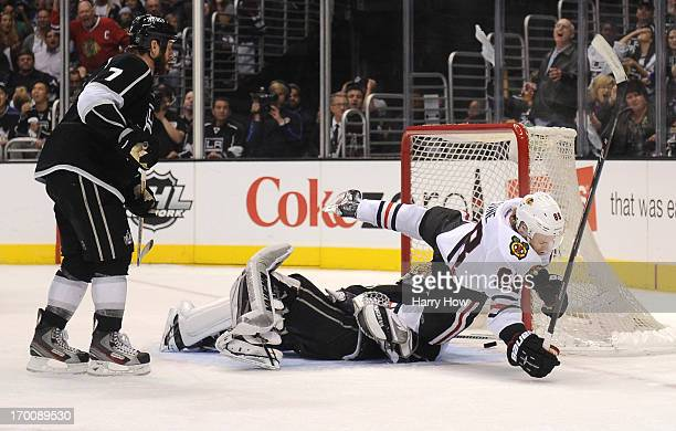 Patrick Kane of the Chicago Blackhawks falls over goaltender Jonathan Quick of the Los Angeles Kings after scoring against Quick in the second period...