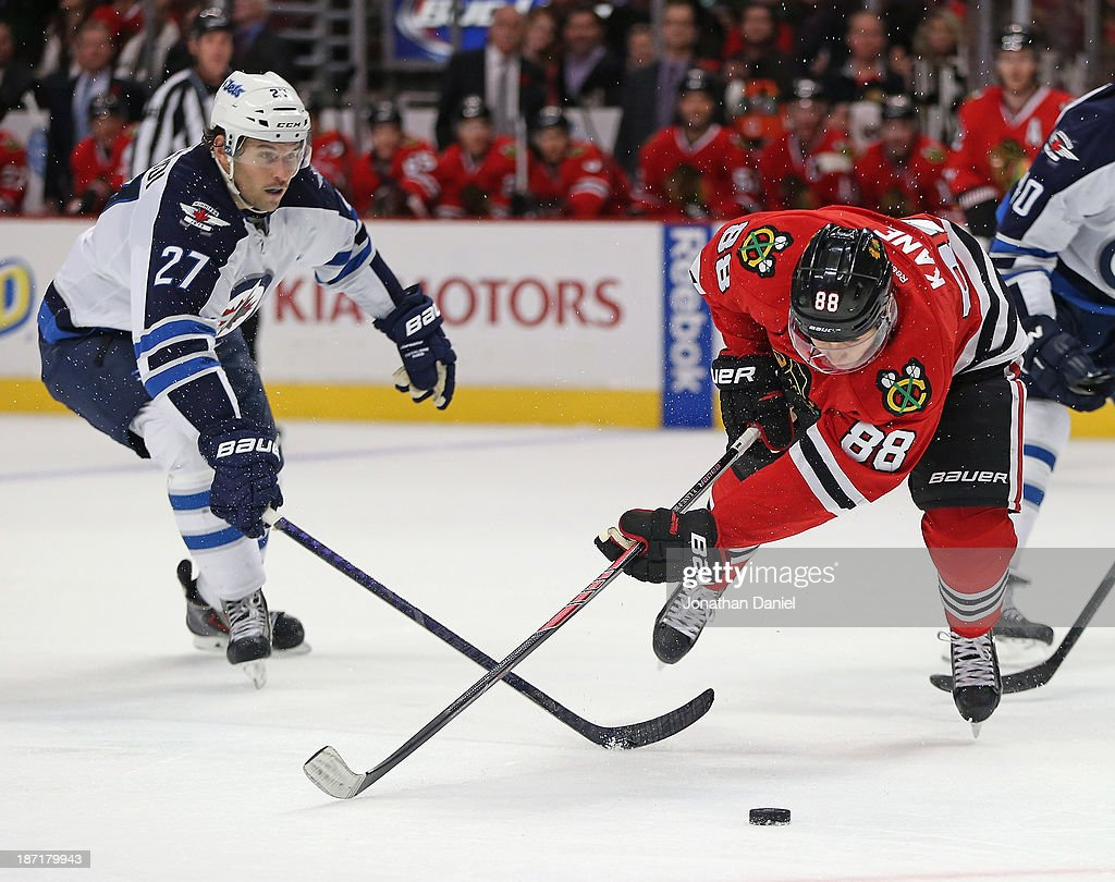 Patrick Kane #88 of the Chicago Blackhawks falls to the ice after being tripped by <a gi-track='captionPersonalityLinkClicked' href=/galleries/search?phrase=Eric+Tangradi&family=editorial&specificpeople=4361715 ng-click='$event.stopPropagation()'>Eric Tangradi</a> #27 of the Winnipeg Jets at the United Center on November 6, 2013 in Chicago, Illinois.