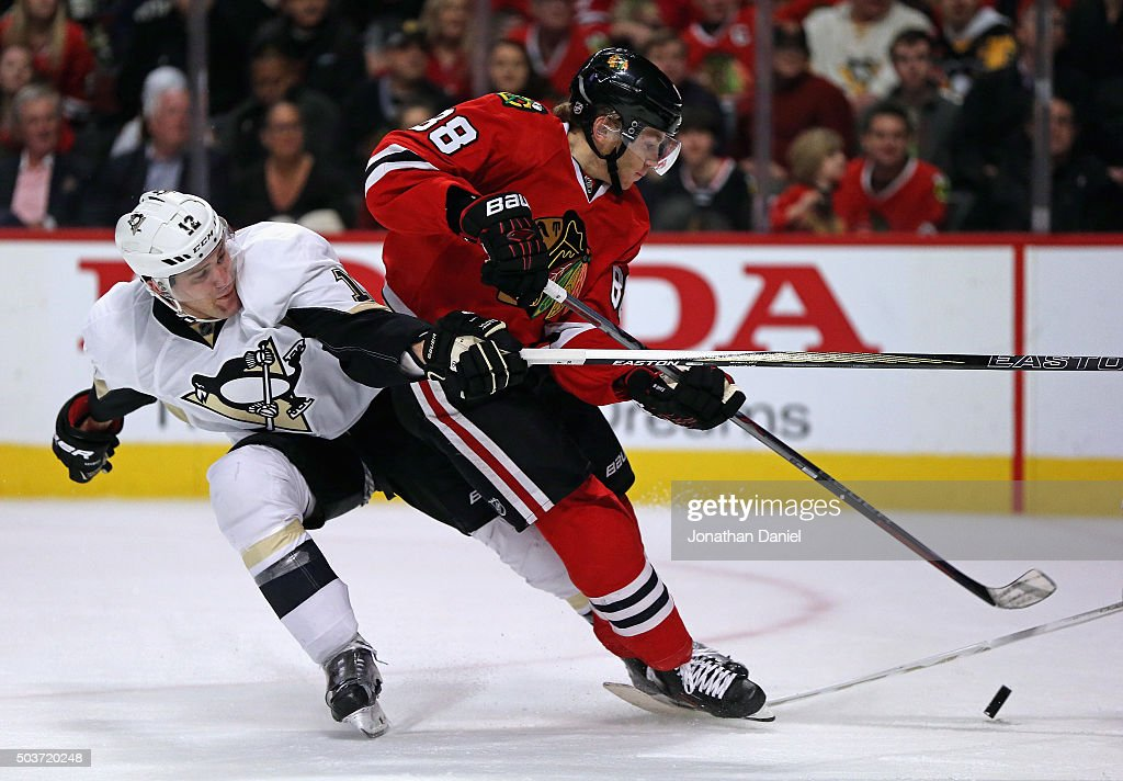 Patrick Kane #88 of the Chicago Blackhawks gets off a shot under pressure from Ben Lovejoy #12 of the Pittsburgh Penguins at the United Center on January 6, 2016 in Chicago, Illinois.