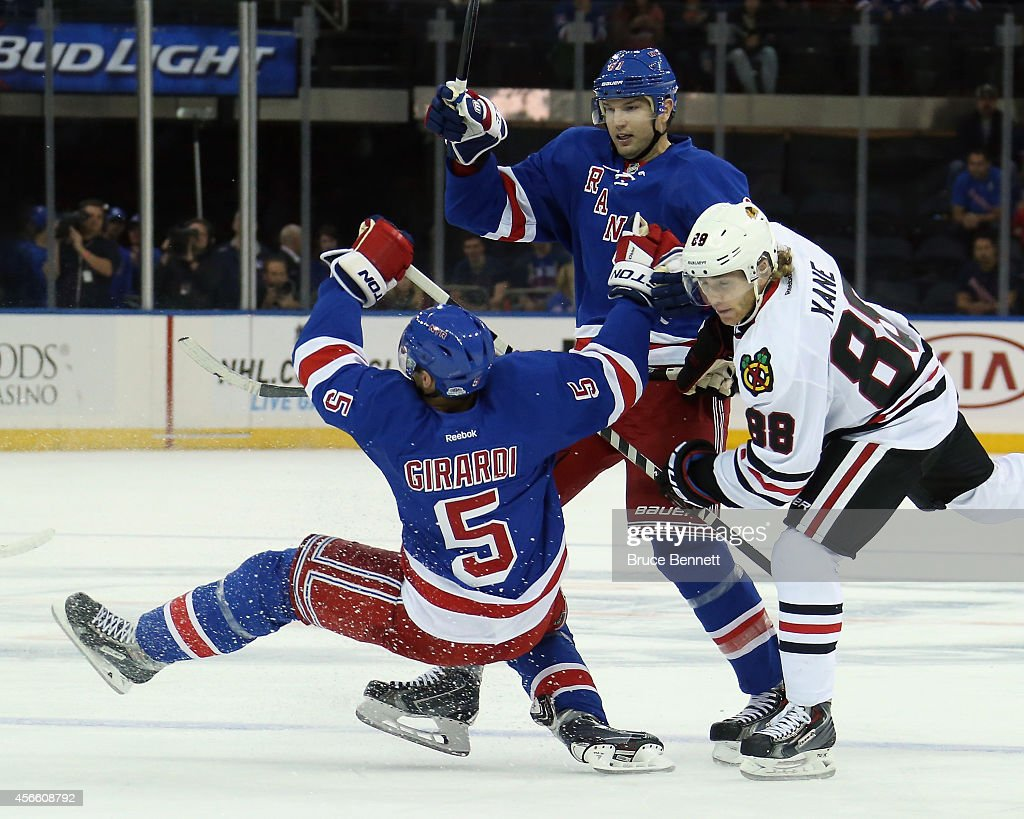 Patrick Kane #88 of the Chicago Blackhawks gets tangled up with Dan Girardi #5 and Rick Nash #61 of the New York Rangers during the first period at Madison Square Garden on October 3, 2014 in New York City.