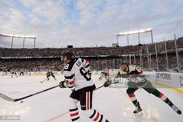 Patrick Kane of the Chicago Blackhawks hits the puck as Marco Scandella of the Minnesota Wild reaches across in the third period of the 2016 Coors...