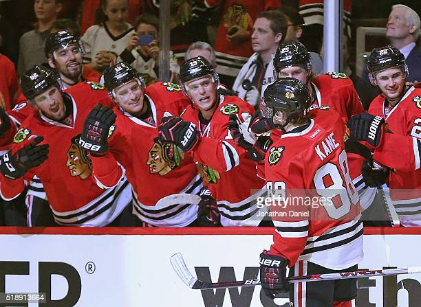Patrick Kane of the Chicago Blackhawks is congratulated by teammates after scoring his third goal of the game in the second period against the Boston...