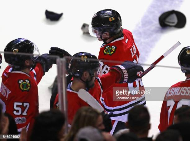 Patrick Kane of the Chicago Blackhawks is congratulated by teammates after scoring a hat trick on an empty net goal in the third period against the...