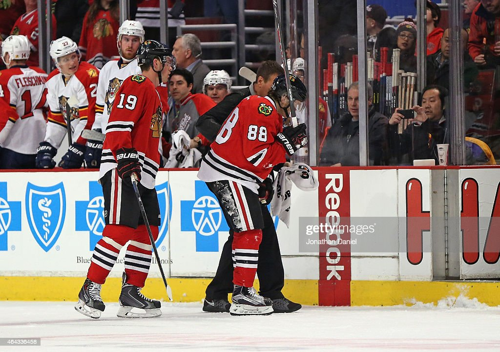 <a gi-track='captionPersonalityLinkClicked' href=/galleries/search?phrase=Patrick+Kane&family=editorial&specificpeople=1977261 ng-click='$event.stopPropagation()'>Patrick Kane</a> #88 of the Chicago Blackhawks is helped off the ice in front of <a gi-track='captionPersonalityLinkClicked' href=/galleries/search?phrase=Jonathan+Toews&family=editorial&specificpeople=537799 ng-click='$event.stopPropagation()'>Jonathan Toews</a> #19 after being cross-checked against the Florida Panthers at the United Center on February 24, 2015 in Chicago, Illinois.