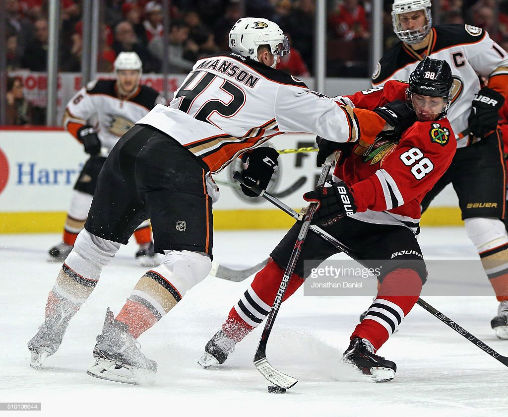 <a gi-track='captionPersonalityLinkClicked' href=/galleries/search?phrase=Patrick+Kane&family=editorial&specificpeople=1977261 ng-click='$event.stopPropagation()'>Patrick Kane</a> #88 of the Chicago Blackhawks is hit while advancing the puck by <a gi-track='captionPersonalityLinkClicked' href=/galleries/search?phrase=Josh+Manson&family=editorial&specificpeople=10214669 ng-click='$event.stopPropagation()'>Josh Manson</a> #42 of the Anaheim Ducks at the United Center on February 13, 2016 in Chicago, Illinois.