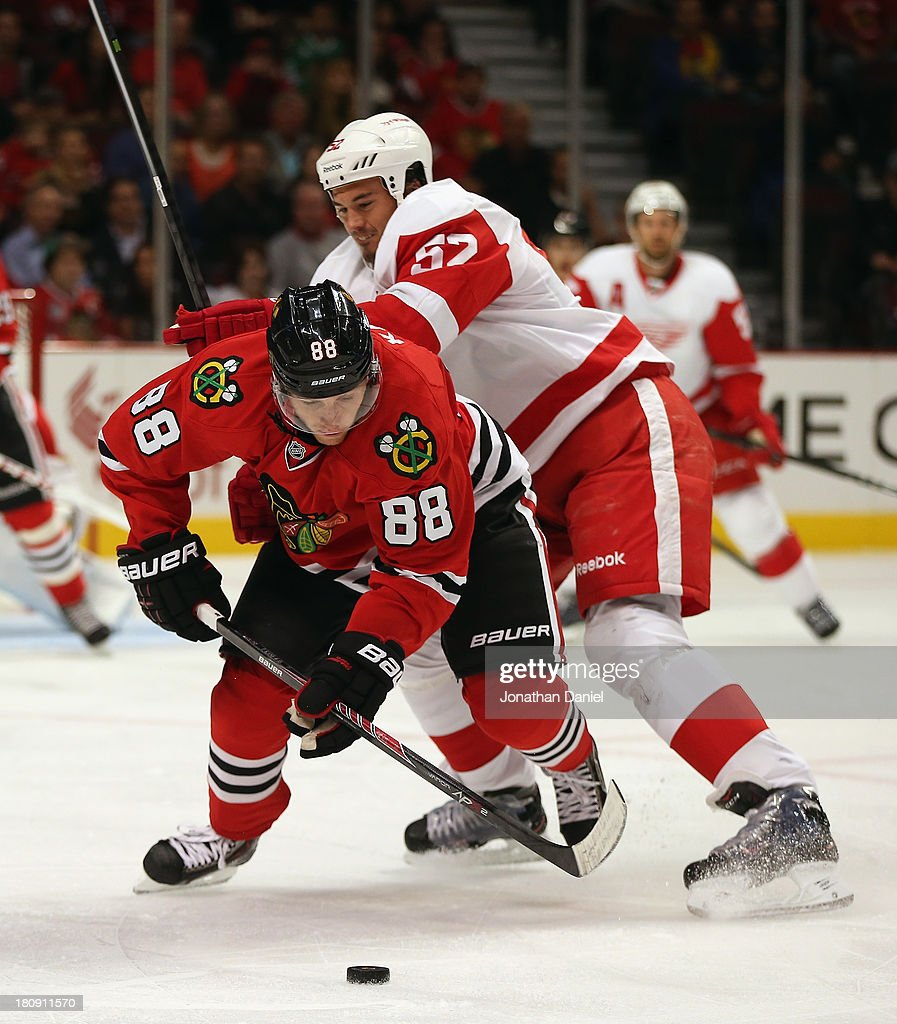 Patrick Kane of the Chicago Blackhawks is shoved from behind by Jonathan Ericsson of the Detroit Red Wings during an exhibition game at United Center...