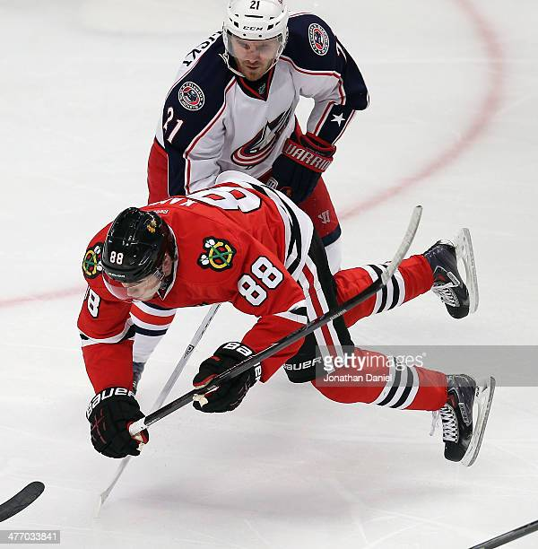 Patrick Kane of the Chicago Blackhawks is tripped by James Wisniewski of the Columbus Blue Jackets at the United Center on March 6 2014 in Chicago...