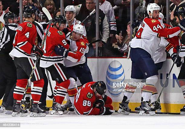 Patrick Kane of the Chicago Blackhawks lays on the ice after being crosschecked as members of the Blackhawks and Florida Panthers tussle after the...