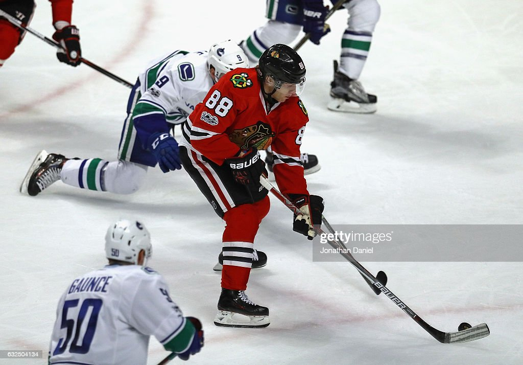 Patrick Kane #88 of the Chicago Blackhawks manuvers between Jack Skille #9 and Brendan Gaunce #50 of the Vancouver Canucks at the United Center on January 22, 2017 in Chicago, Illinois. The Blackhawks defeated the Canucks 4-2.