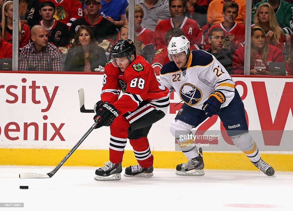 Patrick Kane #88 of the Chicago Blackhawks moves under pressure from Johan Larsson #22 of the Buffalo Sabres at the United Center on October 12, 2013 in Chicago, Illinois. The Blackhawks defeated the Sabres 2-1.