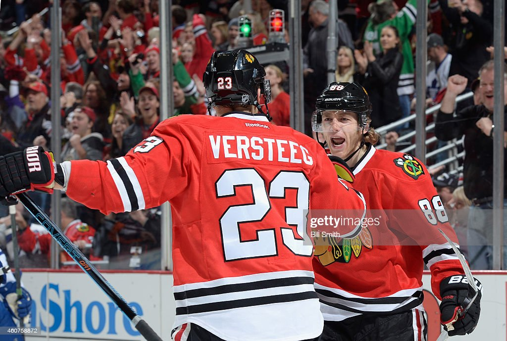 <a gi-track='captionPersonalityLinkClicked' href=/galleries/search?phrase=Patrick+Kane&family=editorial&specificpeople=1977261 ng-click='$event.stopPropagation()'>Patrick Kane</a> #88 of the Chicago Blackhawks reacts after <a gi-track='captionPersonalityLinkClicked' href=/galleries/search?phrase=Kris+Versteeg&family=editorial&specificpeople=2242969 ng-click='$event.stopPropagation()'>Kris Versteeg</a> #23 scored against the Toronto Maple Leafs in the first period during the NHL game at the United Center on December 21, 2014 in Chicago, Illinois.