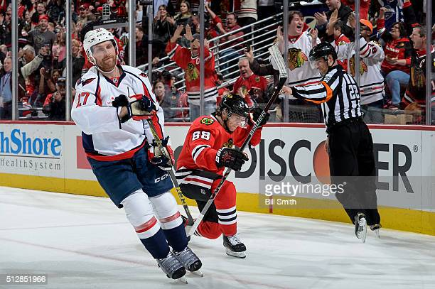 Patrick Kane of the Chicago Blackhawks reacts behind Karl Alzner of the Washington Capitals after scoring in the first period of the NHL game at the...