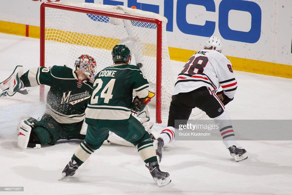 Patrick Kane of the Chicago Blackhawks scores the game winning goal in overtime with Matt Cooke and goalie Ilya Bryzgalov of the Minnesota Wild...