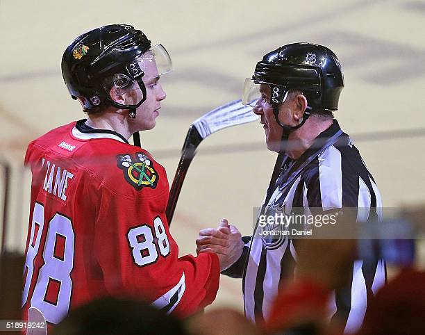 Patrick Kane of the Chicago Blackhawks shakes hands with linesman Andy McElman after McElman worked the last game of his career his 1500th between...
