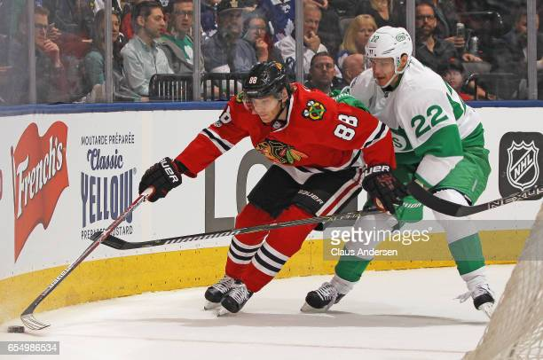 Patrick Kane of the Chicago Blackhawks skates away from a checking Nikita Zaitsev of the Toronto Maple Leafs during an NHL game at the Air Canada...