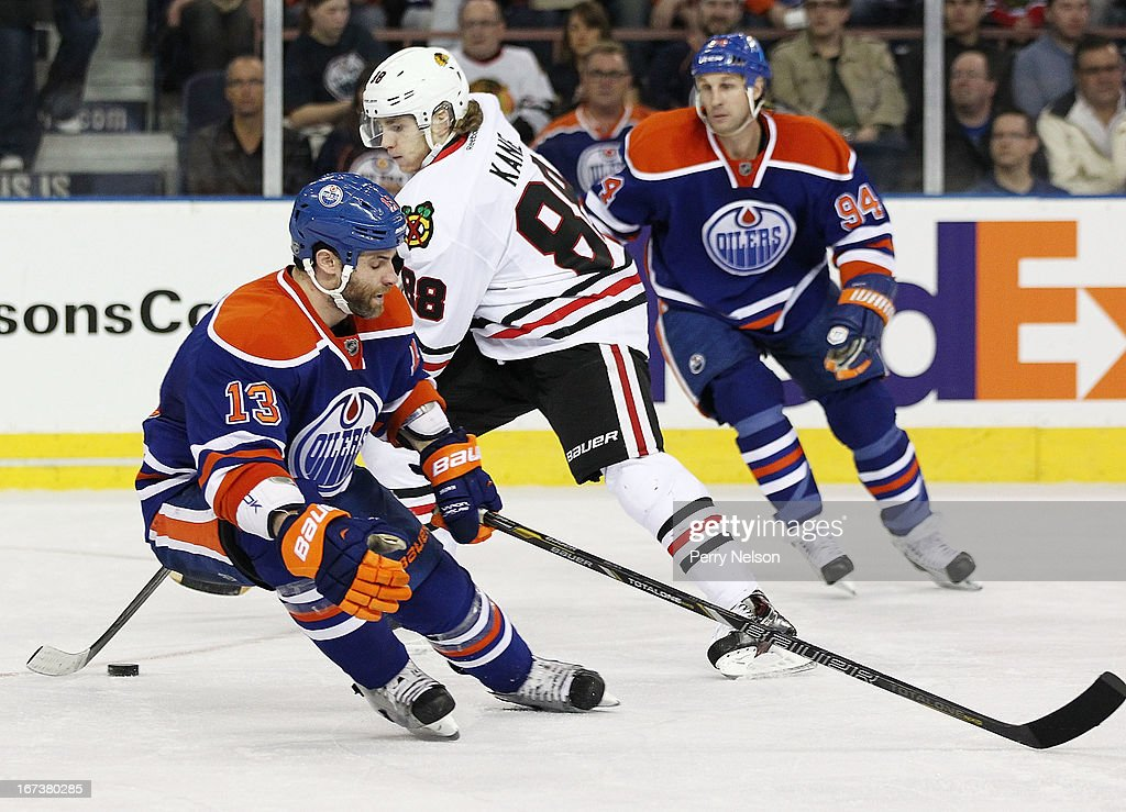 Patrick Kane #88 of the Chicago Blackhawks slides the puck past Mike Brown #13 of the Edmonton Oilers at Rexall Place on April 24, 2013 in Edmonton, Alberta, Canada.
