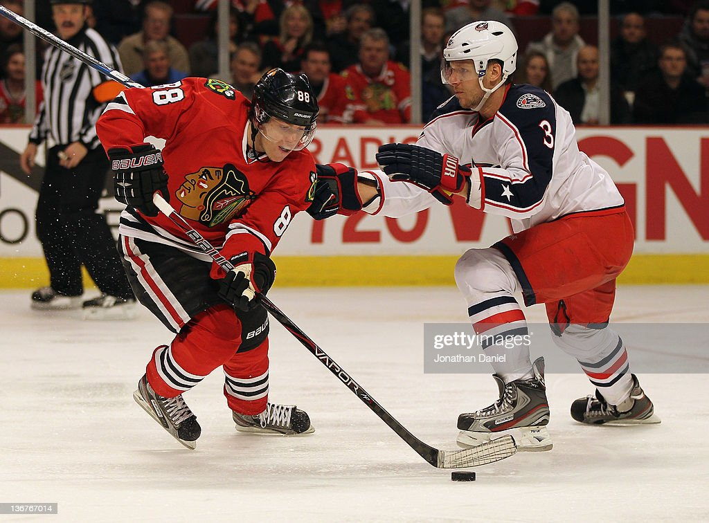 Patrick Kane #88 of the Chicago Blackhawks slips around Derek MacKenzie #24 of the Columbus Blue Jackets at the United Center on January 10, 2012 in Chicago, Illinois. The Blackhawks defeated the Blue Jackets 5-2.