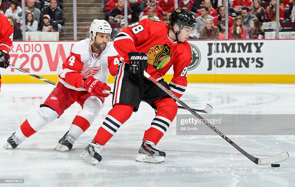 Patrick Kane #88 of the Chicago Blackhawks takes control of the puck as <a gi-track='captionPersonalityLinkClicked' href=/galleries/search?phrase=Todd+Bertuzzi&family=editorial&specificpeople=202476 ng-click='$event.stopPropagation()'>Todd Bertuzzi</a> #44 of the Detroit Red Wings follows behind during the NHL game on January 27, 2013 at the United Center in Chicago, Illinois.