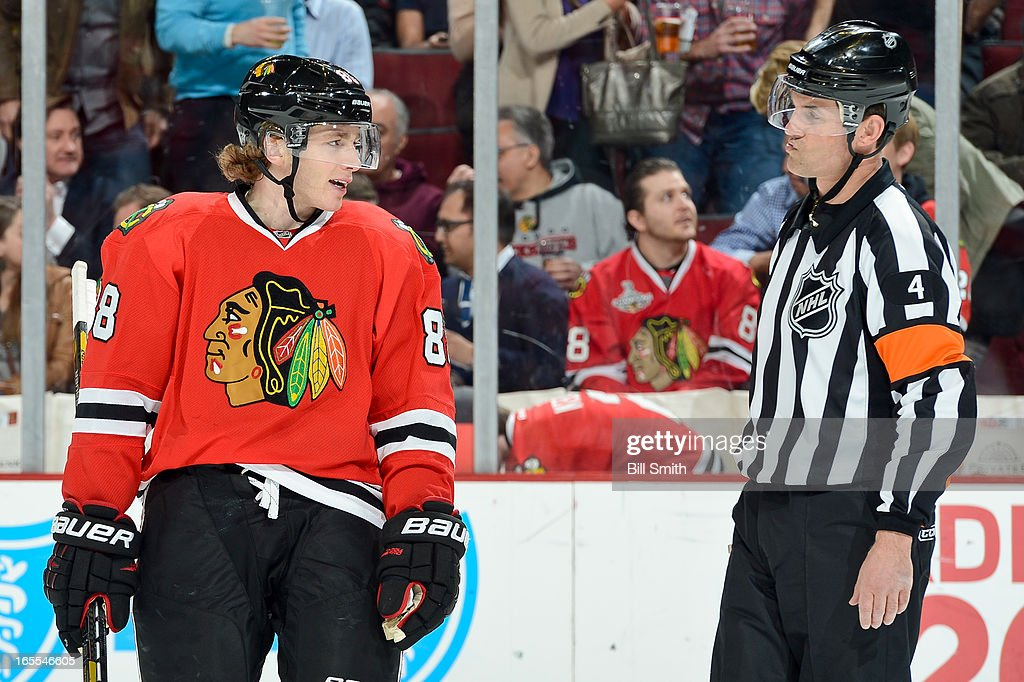 Patrick Kane #88 of the Chicago Blackhawks talks with referee Wes McCauley #4 during the NHL game against the St. Louis Blues on April 04, 2013 at the United Center in Chicago, Illinois.