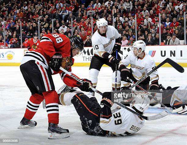 Patrick Kane of the Chicago Blackhawks tries to get at the puck as Matt Beleskey of the Anaheim Ducks lays on the ice and Corey Perry of the Ducks...