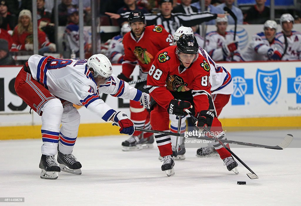Patrick Kane #88 of the Chicago Blackhawks tries to get off a shot under pressure from <a gi-track='captionPersonalityLinkClicked' href=/galleries/search?phrase=Marc+Staal&family=editorial&specificpeople=3809026 ng-click='$event.stopPropagation()'>Marc Staal</a> #18 of the New York Rangers at the United Center on January 8, 2014 in Chicago, Illinois. The Rangers defeated the Blackhawks 3-2.