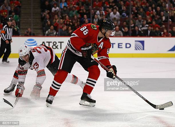 Patrick Kane of the Chicago Blackhawks turns to pass as Yohann Auvitu of the New Jersey Devils falls behind him at the United Center on December 1...