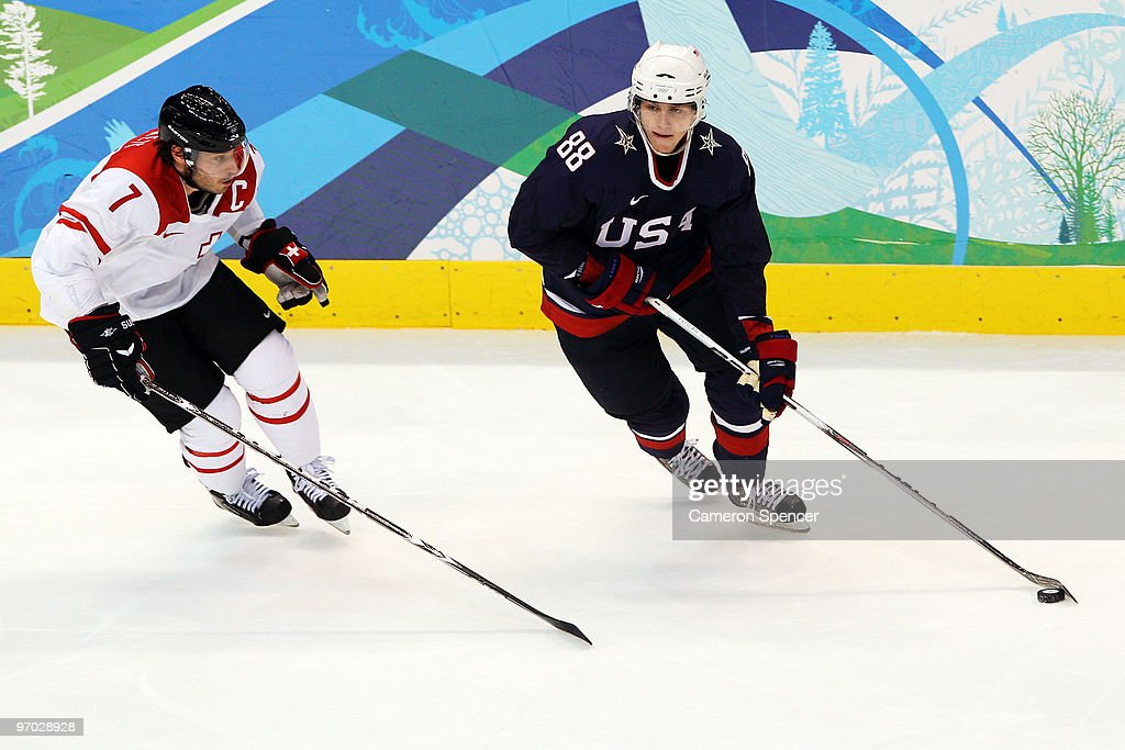 Patrick Kane of the United States battles for the puck with Mark Streit of Switzerland during the ice hockey men's quarter final game between USA and...