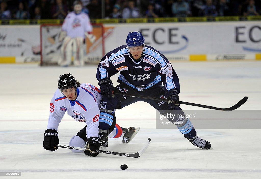 Patrick Koppchen of Hamburg is challenged by <a gi-track='captionPersonalityLinkClicked' href=/galleries/search?phrase=Daniel+Weiss+-+Ice+Hockey+Player&family=editorial&specificpeople=1259829 ng-click='$event.stopPropagation()'>Daniel Weiss</a> of the Ice Tiger during the DEL game between Hamburg Freezers and Thomas Sabo Ice Tigers at O2 World on January 25, 2013 in Hamburg, Germany.