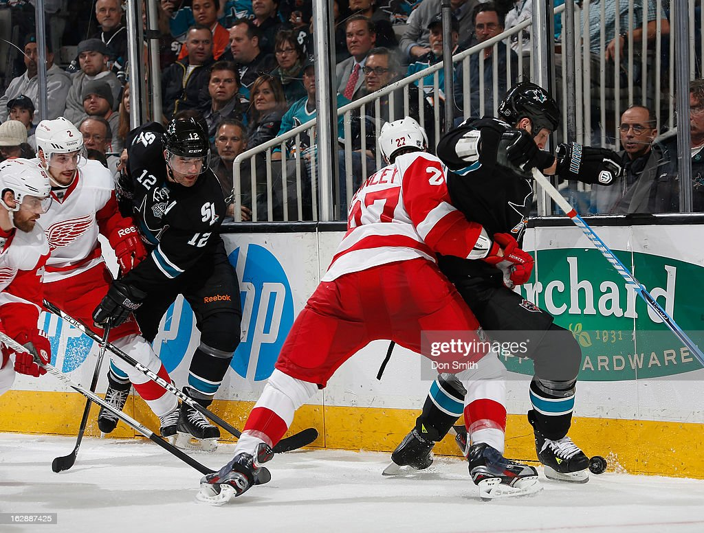 Patrick Marleau #12 and Ryane Clowe #29 of the San Jose Sharks battle for the puck against Kyle Quincey #27 and Brendan Smith #2 of the Detroit Red Wings during an NHL game on February 28, 2013 at HP Pavilion in San Jose, California.