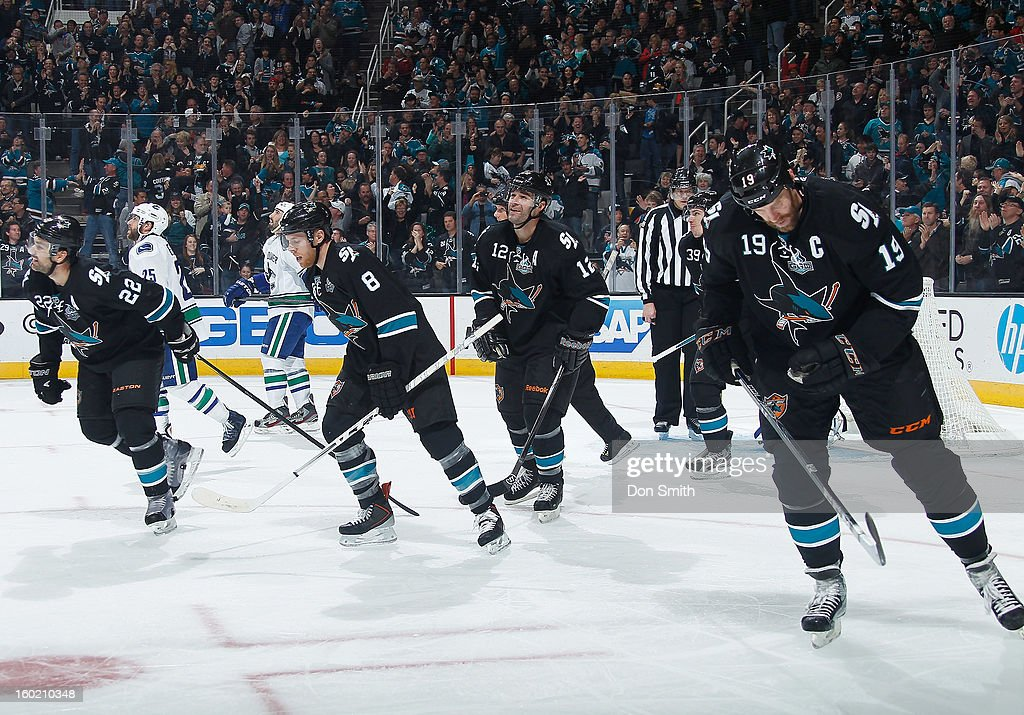Patrick Marleau #12, Joe Thornton #19, Joe Pavelski #8 and Dan Boyle #22 of the San Jose Sharks head back to the bench for high fives after Marleau's goal against the Vancouver Canucks during an NHL game on January 27, 2013 at HP Pavilion in San Jose, California.