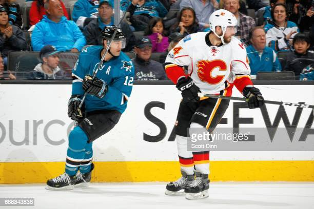 Patrick Marleau of the San Jose Sharks and Matt Bartkowski of the Calgary Flames look during a NHL game at SAP Center at San Jose on April 8 2017 in...