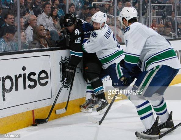 Patrick Marleau of the San Jose Sharks battles for the puck against Dan Hamhuis and Kevin Bieksa of the Vancouver Canucks in Game Four of the Western...